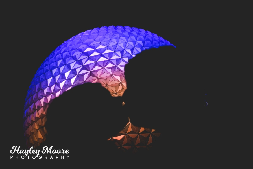 photo of couple kissing in front of purple and pink large object at night