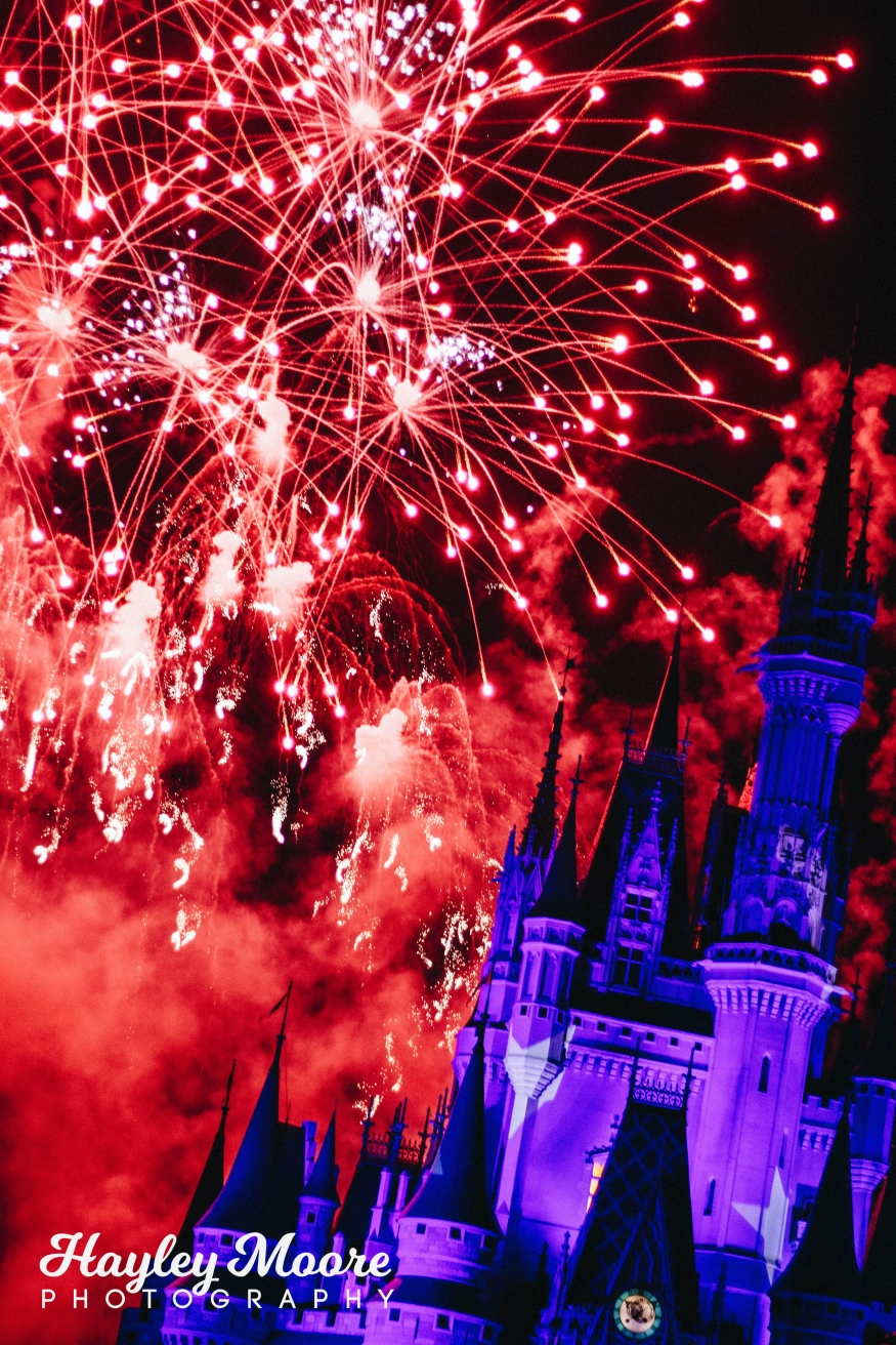 photo of red fireworks in front of blue castle