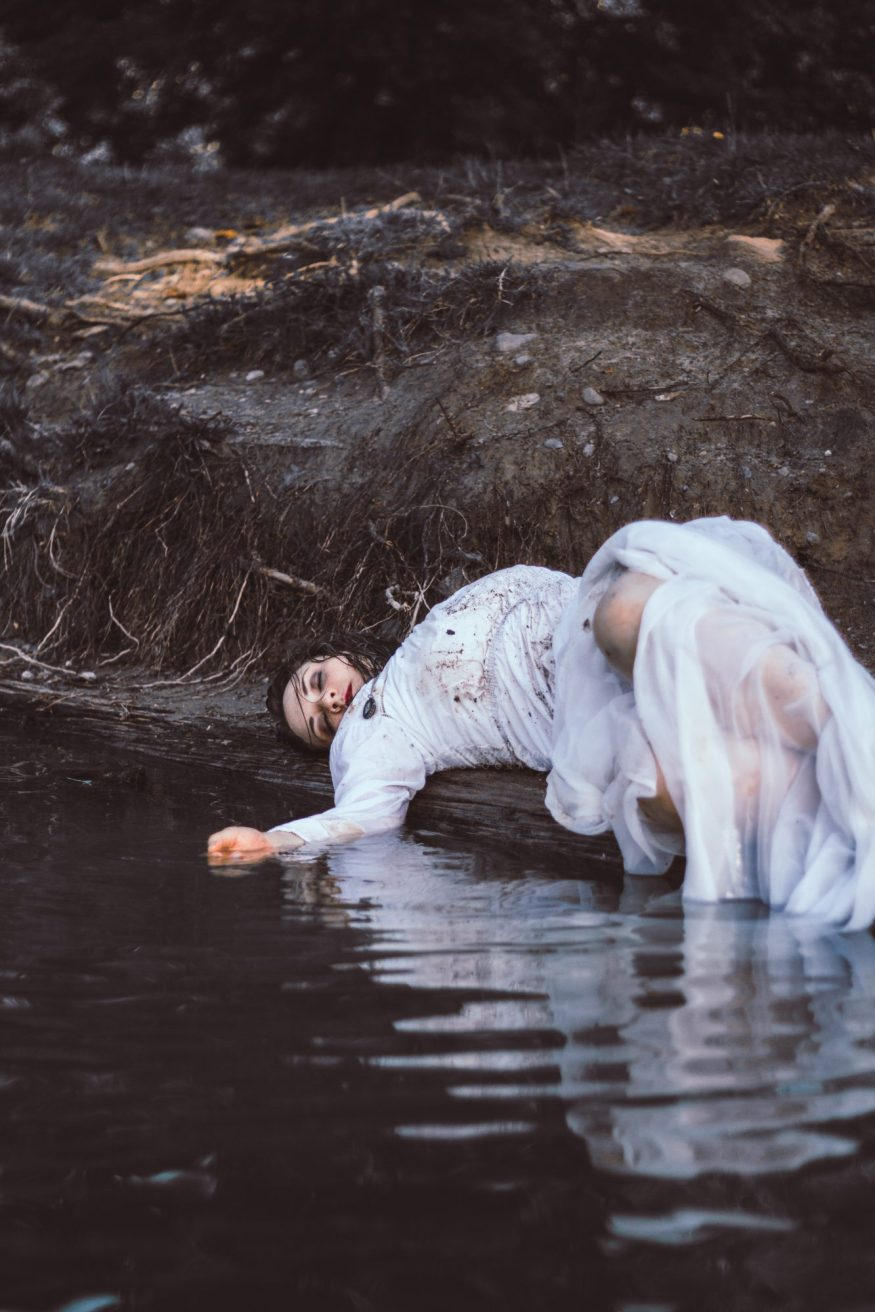 Portrait of a woman laying by water