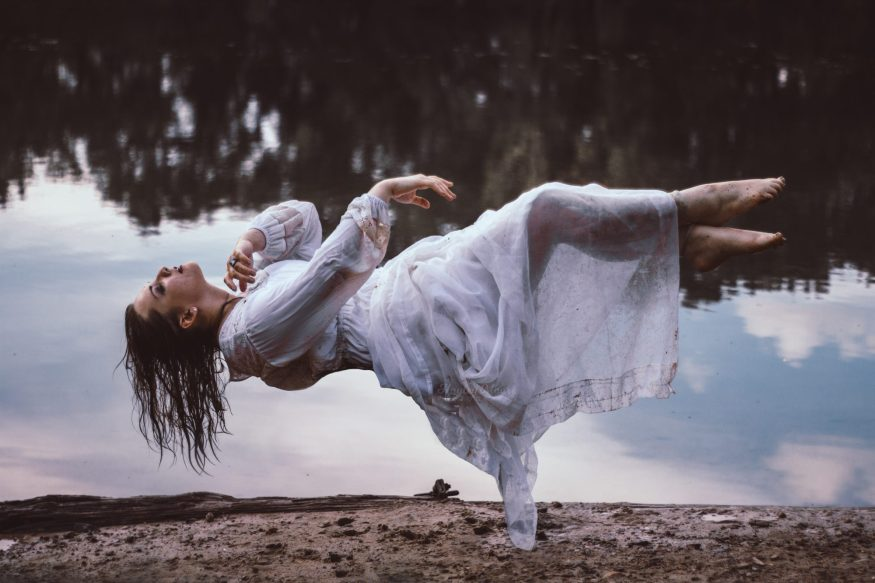 Portrait of a woman levitating by water