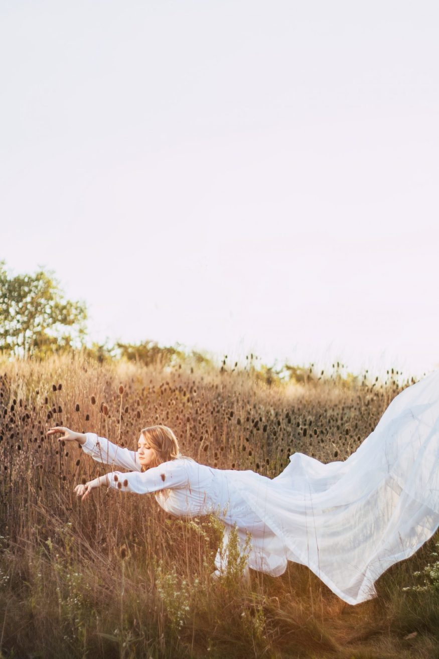 Portrait of a woman levitating in field