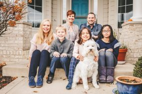 Family of six with white poodle dog on porch
