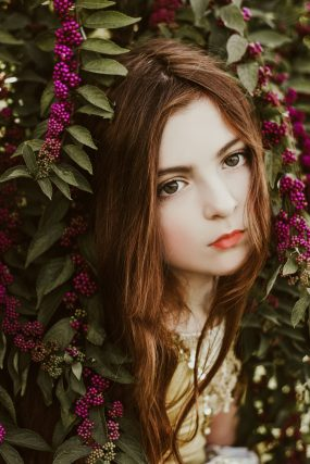 Portrait of young girl in a garden bush