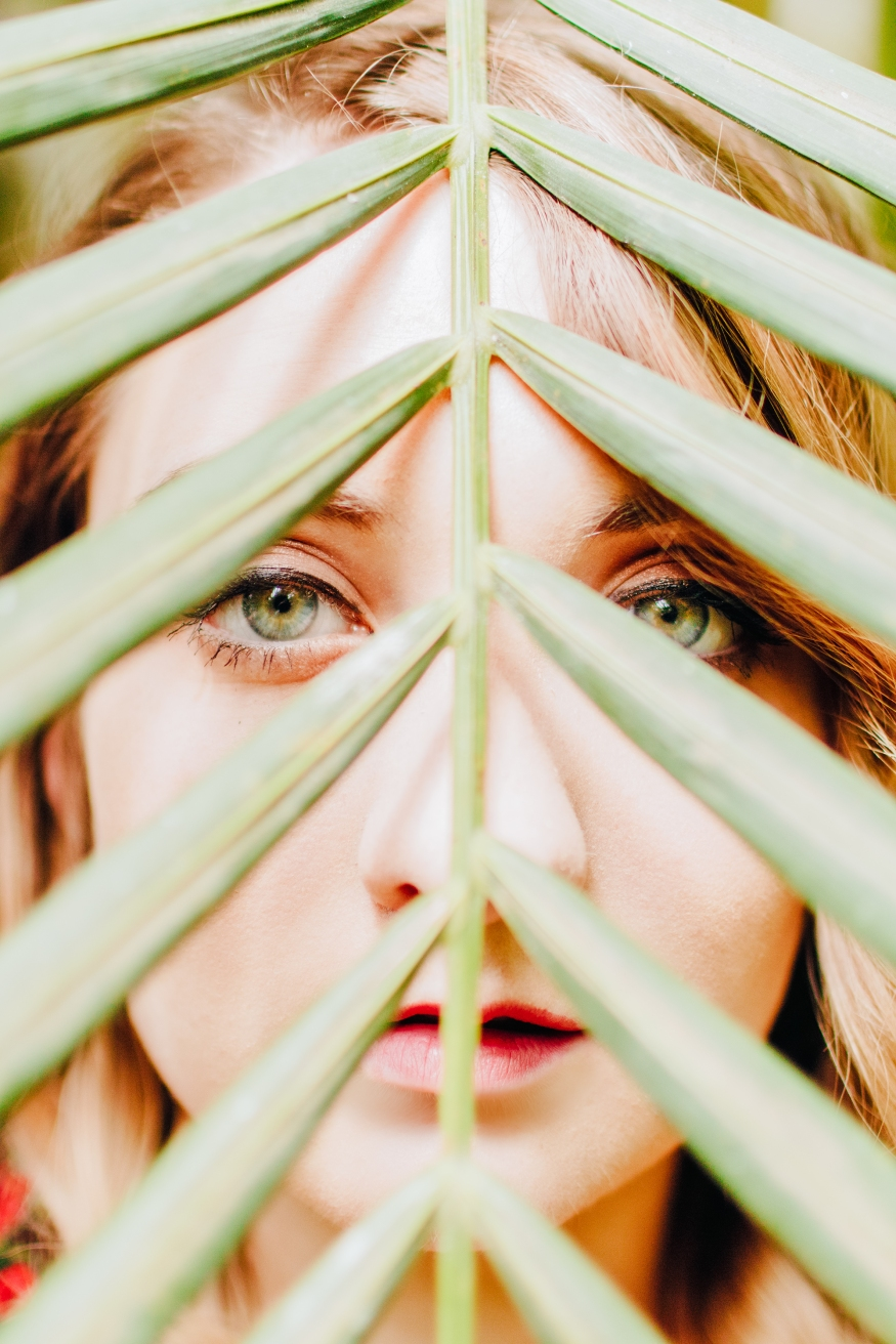 Model with green eyes with leaf in front of face