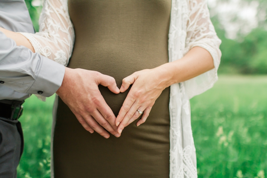 Portrait of expecting mother with heart shaped hands on belly