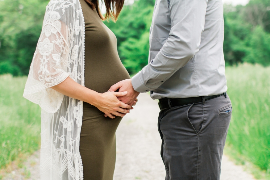 Portrait of expecting couple holding belly