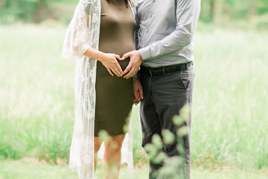 Portrait of expecting couple making heart with hands on belly
