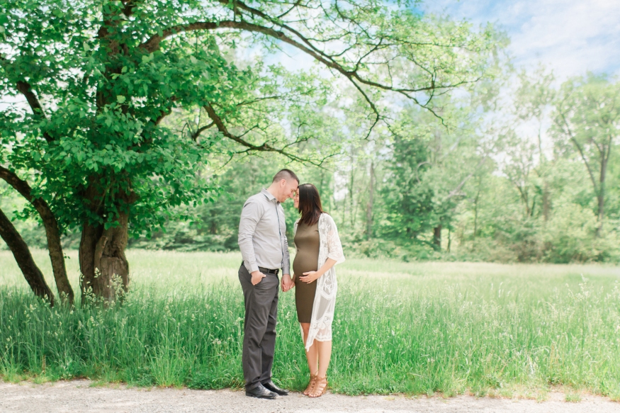 Portrait of expecting couple by tree